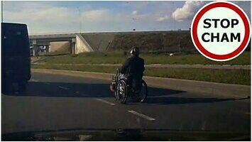 Turbowózek inwalidzki lawiruje między autami