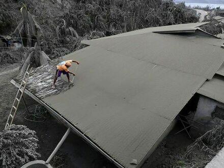 To zdjęcie zostało wykonane w kolorze. Mieszkaniec Laurel czyści swój dach z popiołu, Filipiny.